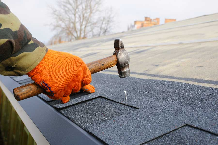 Worker Hands Installing Bitumen Roof Shingles Using Hammer In Nails